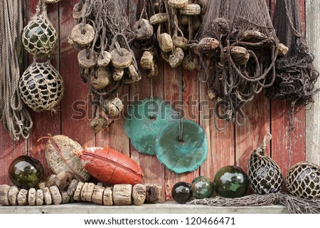 Closeup of old fishing nets, green rounded stone sinkers and glass floats in a glimpse of sunlight. - stock photo