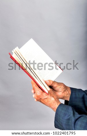 Closeup of old man hands holding an open book over gray background