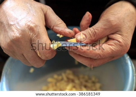 Closeup of old man's hands while he is slicing potatoes
