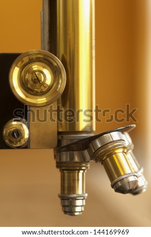 closeup of old microscope lenses or vintage scientific equipment - stock photo