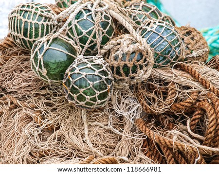 Closeup of old netted green glass float hanging on wall in Norway - stock photo