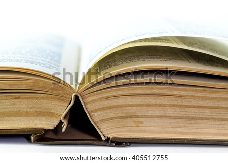 Closeup of old open book fading away to white background