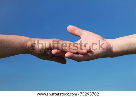 closeup of old people holding for hands, blue sky - stock photo