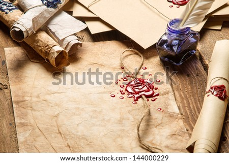 Closeup of old rolls of paper, glasses and blue ink in the inkwell - stock photo