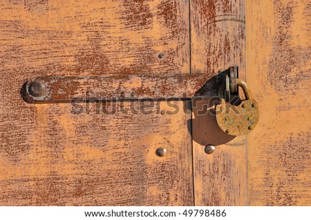 Closeup of old rusty padlock on metal background - stock photo