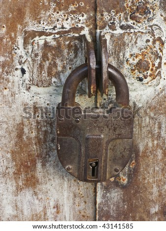 Closeup of old rusty padlock on metal gate background - stock photo