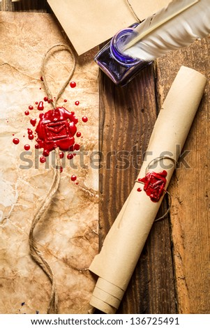 Closeup of old scrolls,  sealing wax and blue ink on wooden table - stock photo