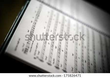 Closeup of old sheet music in dark background - stock photo