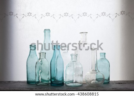 Closeup of old small glass bottles at windowsill against daylight - stock photo