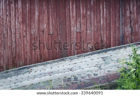 Closeup of old worn row boat laying upside down at red wooden wall at summer. Photographed at Helgeland, Norway. - stock photo