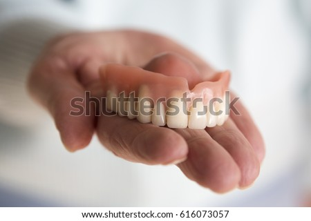 closeup of older womans hand holding a teeth denture