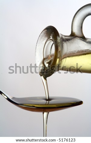 Closeup of olive oil being poured from a carafe onto and overflowing a spoon - stock photo