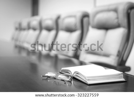 Closeup of  on table in empty corporate conference room before business meeting in office, black and white style - stock photo
