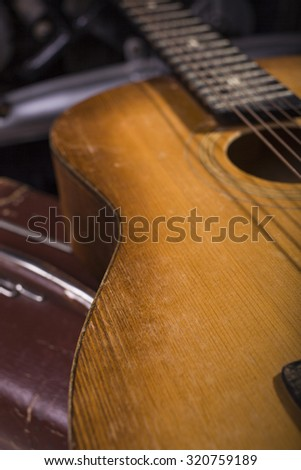 Closeup of one acoustic string light brown color wooden musical instrument of guitar with beautiful shape indoor in studio, vertical picture - stock photo