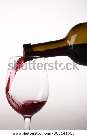 Closeup of one beautiful clear glass goblet with pouring from green bottle tasty sweet red dessert grape wine with bubbles in standing position isolated on white studio background, vertical picture - stock photo