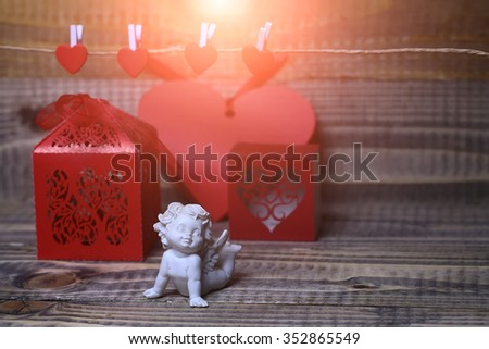 Closeup of one beautiful cupid angel decorative figurine near red paper greeting valentine box near clothes-peg in shape of heart with no people on wooden background copy space, horizontal picture - stock photo