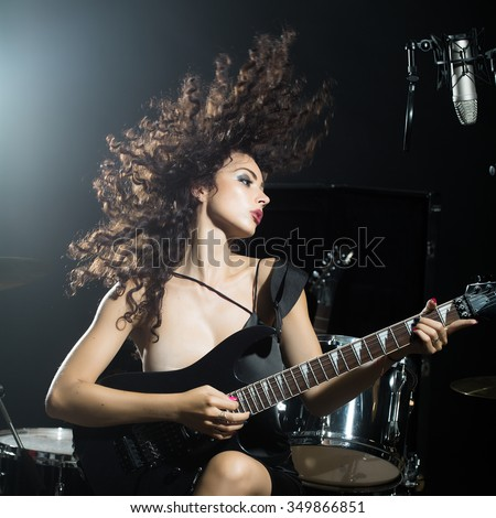 Closeup of one beautiful emotional expressive cool young brunette sexual rock musician woman with long curly hair sitting in recording studio playing electro guitar singing near drums and microphone - stock photo