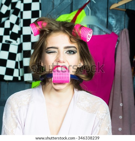 Closeup of one beautiful young fashionable emotional surprised woman in dressing gown with hair-rollers on head and in mouth standing in wardrobe among many bright clothes, square picture - stock photo