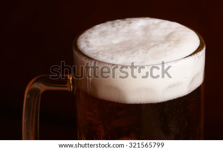 Closeup of one big glass goblet full of dark tasty frothy alcoholic beverage of beer standing on black background, horizontal picture - stock photo