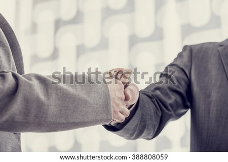 Closeup of one businessman giving money or bribe to the other in a gesture of handshake, vintage effect toned image. - stock photo