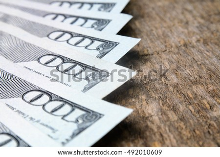 closeup of one hundred dollars on wooden table