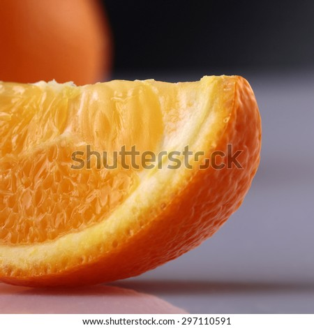 Closeup of one lobule of fresh juicy ripe appetizing orange in front lying on grey reflecting surface in studio isolated on black background, square picture - stock photo