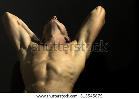 Closeup of one young sexual undressed man with beautiful muscular strong body and torso standing with raised hands in studio on black wall background, horizontal picture - stock photo