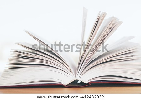 Closeup of open book on wooden desktop - stock photo