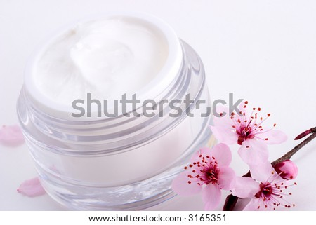 Closeup of open container of moisturizing face cream and blooming twig of plum on white background with small pink petals around - stock photo