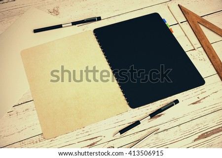 Closeup of open notepad with black and beige pages placed on light wooden desktop with other office tools. Mock up, 3D Rendering - stock photo