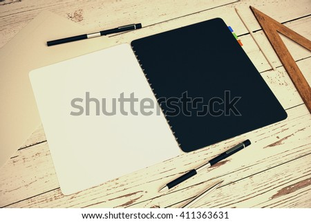 Closeup of open notepad with black and white pages placed on light wooden desktop with other office tools. Mock up, 3D Rendering - stock photo