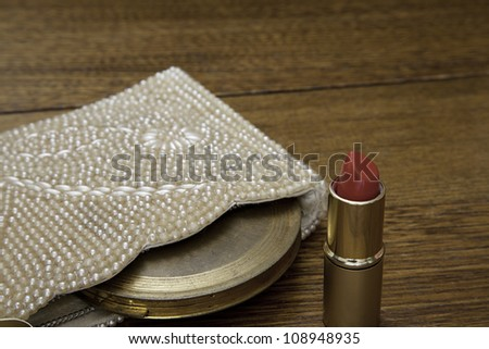 Closeup of open red lipstick tube with 1920s purse containing vintage powder compact on oak dressing table.