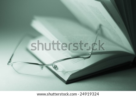 closeup of opened book and glasses