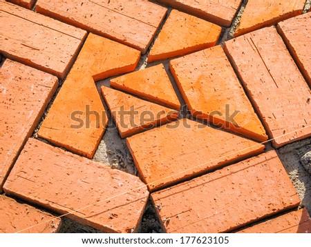 Closeup of orange brick paving stones pattern in the construction process - stock photo