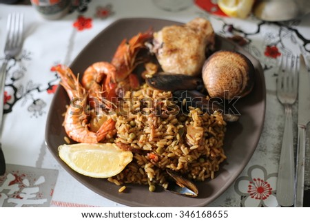 Closeup of paella with seafood and chicken on a table, selective focus - stock photo