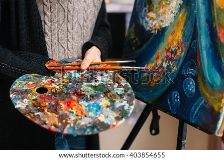 Closeup of paintbrushes and stained mixing  palette in woman hands. Unrecognizable female artist in a workshop holding a stained palette and brush. Closeup of painting tools - stock photo