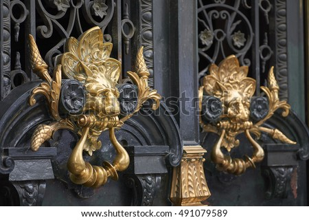 Closeup Of Pair Of Ornate Golden Lion Head Door Knockers
