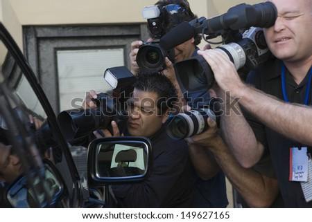 Closeup of paparazzi photographers at car window - stock photo