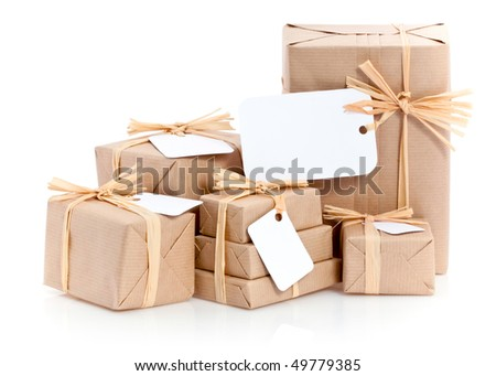 Closeup of parcels in brown wrapping paper and blank tags or labels isolated on white background - stock photo