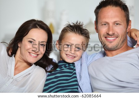 Closeup of parents and child relaxing at home on sofa - stock photo