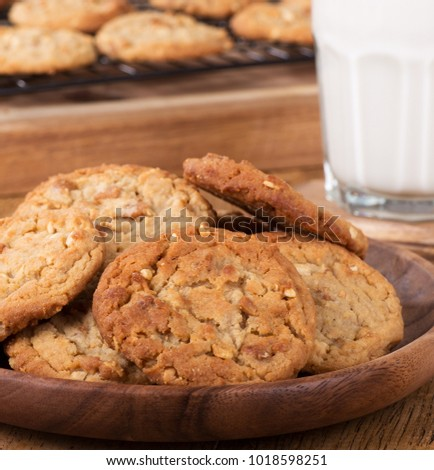 Closeup of peanut butter cookies on a wooden plate with cookies on a cooling rack and glass of milk in background