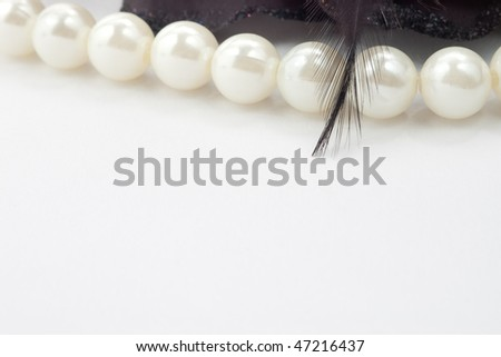 Closeup of pearl necklace with black feather and selective focus - stock photo