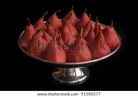 Closeup of pears poached in red wine and served in a silver colored bowl. A traditional Christmas dish in the Netherlands. - stock photo