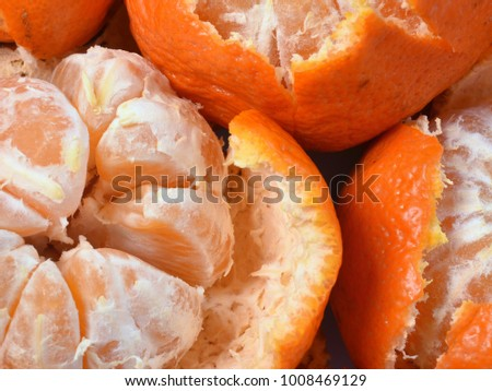 Closeup of peeled fresh tangerine, orange slices with white veins, thick peel.