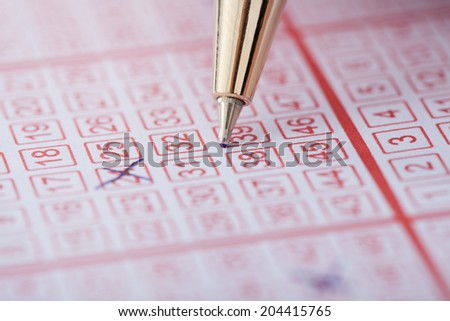 Closeup of pen marking numbers on lottery ticket - stock photo