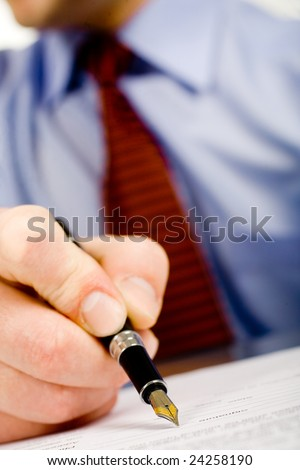 Closeup of pen with plume signing signature in document bottom