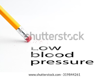 Closeup of pencil eraser and black low blood pressure text. Low blood pressure. Pencil with eraser. - stock photo