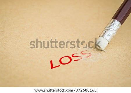 Closeup of pencil eraser and the word LOSS, soft focus - stock photo