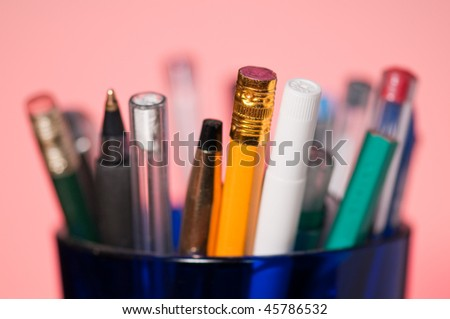 Closeup of pencils and pens in blue glass - shallow dof