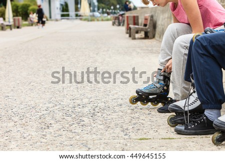 Closeup of people friends putting on roller skates outdoor. Woman and man sitting on bench.